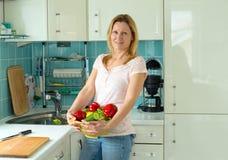 Blonde Frau, die in der Küche steht Stockfoto