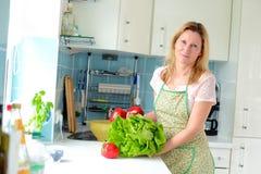 Blonde Frau, die in der Küche steht Lizenzfreie Stockfotografie