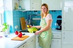 Blonde Frau, die in der Küche steht Lizenzfreies Stockfoto