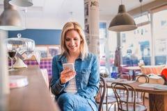 Blonde Frau, die an der Stange, schreibend am Telefon sitzt Stockfotos