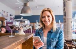Blonde Frau, die an der Stange, schreibend am Telefon sitzt Lizenzfreie Stockfotografie
