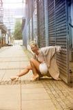 Blonde Frau, die in der Straße lacht Stockbilder