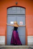 Blonde Frau, die in der Tür aufwirft Stockbilder