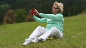 Blonde Frau, die in der Wiese auf grünem Gras sitzt und Fotos macht stock video