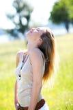 Blonde Frau, die in der Wiese genießt Sonne steht Lizenzfreies Stockfoto