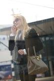 Blonde Frau, die draußen am Handy spricht Stockfotos