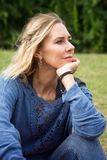 Blonde Frau, die draußen im Park sitzt Stockfotos