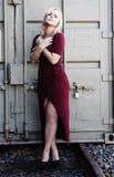 Blonde Frau, die draußen roten Kleiderkanister steht Stockfotos