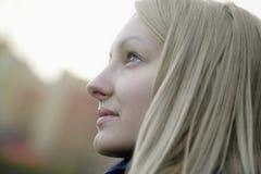 Blonde Frau, die draußen weg schaut Stockfoto
