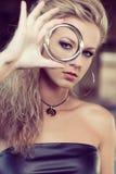 Blonde Frau, die durch Armband schaut Lizenzfreie Stockfotografie