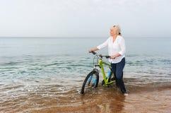 Blonde Frau, die durch das Meer mit einem Fahrrad watet Lizenzfreie Stockbilder