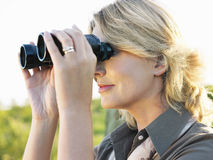 Blonde Frau, die durch Ferngläser schaut Stockbild