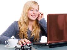 Blonde Frau, die durch Telefon und Arbeitso benennt Stockbilder