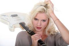 Blonde Frau, die E-Gitarre hält Lizenzfreie Stockbilder