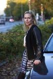 Blonde Frau, die ein Auto bereitsteht Stockbilder