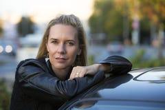 Blonde Frau, die ein Auto bereitsteht Lizenzfreies Stockbild