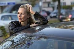 Blonde Frau, die ein Auto bereitsteht Lizenzfreies Stockfoto