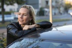 Blonde Frau, die ein Auto bereitsteht Lizenzfreie Stockbilder