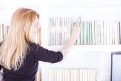 Blonde Frau, die ein Bibliotheksbuch vom Regal abzieht Lizenzfreies Stockfoto