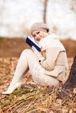 Blonde Frau, die ein Buch liest stockbilder