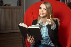 Blonde Frau, die ein Buch liest Stockfotografie