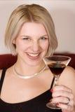 Blonde Frau, die ein Cocktailglas anhält Stockfotos