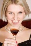 Blonde Frau, die ein Cocktailglas anhält Lizenzfreies Stockfoto