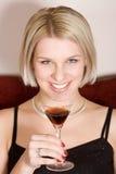 Blonde Frau, die ein Cocktailglas anhält Lizenzfreie Stockbilder