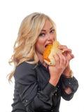 Blonde Frau, die ein Feinkostgeschäftsandwich isst Lizenzfreies Stockbild