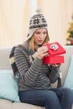 Blonde Frau, die ein Geschenk sitzt auf einem Sofa öffnet Stockbild