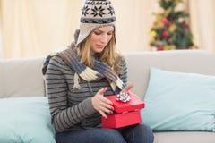 Blonde Frau, die ein Geschenk sitzt auf einem Sofa öffnet Stockfotografie