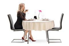 Blonde Frau, die ein Glas Rotwein riecht Lizenzfreie Stockfotografie