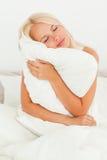 Blonde Frau, die ein Kissen anhält Lizenzfreie Stockfotos