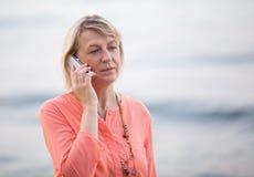 Blonde Frau, die ein Telefongespräch im Freien hat Stockbild