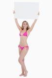 Blonde Frau, die ein unbelegtes Plakat über ihrem Kopf anhebt Lizenzfreie Stockfotos