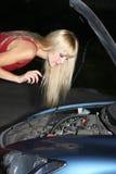 Blonde Frau, die ein unterbrochenes Auto repariert Stockfoto