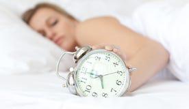 Blonde Frau, die eine Alarmuhr anhält Stockfotos