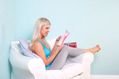 Blonde Frau, die eine Geburtstagkarte öffnet Lizenzfreie Stockfotos