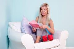 Blonde Frau, die eine Geburtstagkarte öffnet Lizenzfreie Stockbilder