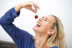 Blonde Frau, die eine Kirsche isst Lizenzfreies Stockfoto
