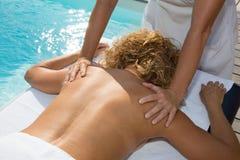 Blonde Frau, die eine Rückenmassage in einer Badekurortmitte hat Lizenzfreie Stockfotos