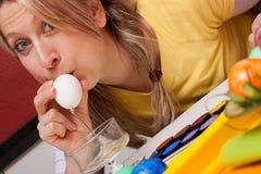 Blonde Frau, die in eine Schüssel des Eies durchbrennt Stockfoto