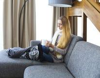 Blonde Frau, die eine Schale warmen Tee bei der Entspannung auf dem Sofa hält Lizenzfreie Stockfotos
