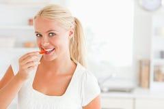 Blonde Frau, die eine Scheibe des Pfeffers isst Stockbild
