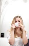 Blonde Frau, die eine Tasse Tee genießt Stockbild
