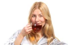 Blonde Frau, die eine Tasse Tee trinkt Lizenzfreie Stockbilder