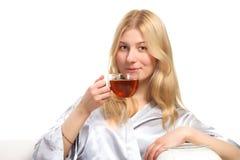 Blonde Frau, die eine Tasse Tee trinkt Stockbilder