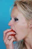 Blonde Frau, die eine Tomate isst Lizenzfreie Stockfotografie