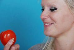 Blonde Frau, die eine Tomate isst Lizenzfreie Stockfotos