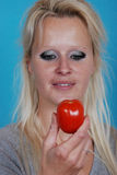 Blonde Frau, die eine Tomate isst Stockbild